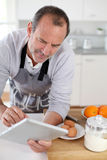 Senior man in the kitchen searching for recipe with tablet. Senior men in kitchen using electronic tablet Royalty Free Stock Photos