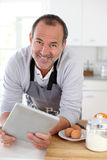 Senior man in the kitchen searching for recipe on tablet Royalty Free Stock Images