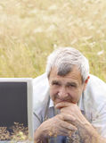 Senior man with laptop. On the meadow Royalty Free Stock Images