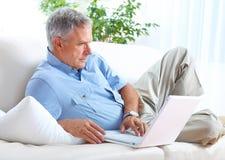 Senior man with laptop. Smiling elderly senior man with laptop at home stock photos