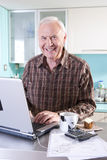 Senior man with laptop computer in kitchen, portrait Stock Images