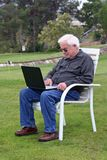 Senior man with laptop at golf. Elderly man, senior citizen, using a laptop at a golf course, sitting on a white chair Royalty Free Stock Photo