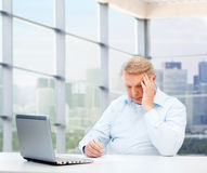 Senior man with laptop and pen writing at office Royalty Free Stock Photography