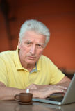 Senior man with laptop. Senior man sitting with laptop and coffee in hotel Royalty Free Stock Photo