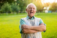 Senior man is laughing. Male with crossed arms outdoor. What a witty joke. You raised my mood Royalty Free Stock Image