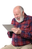Senior man laughing with something at screen of tablet computer, isolated on white. Senior bald and bearded white haired man laughing loud with something at stock photos