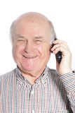 Senior man laughing while talking on phone Royalty Free Stock Photography