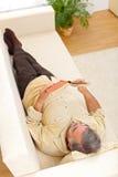 Senior man laying and reading Royalty Free Stock Photo
