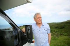 Senior man leaning on camping car Royalty Free Stock Photo