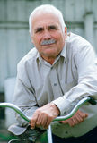 Senior man leaning on the handlebar of his bicycle Stock Image