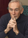 Senior man leaning on his hands, deep in thought Stock Images