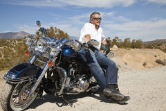 Senior man leaning on motorcycle on desert road Stock Images