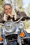 Senior man leaning on motorcycle handlebars Royalty Free Stock Photo