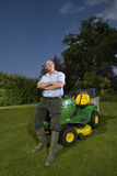 Senior man leaning on riding lawn mower Stock Images