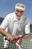 Senior Man Leaning On Tennis Net Royalty Free Stock Images