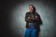 Senior man in leather jacket posing in gray studio Royalty Free Stock Image