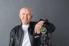 Senior man in leather jacket standing isolated on gray leaning on camera on tripod smiling playful close-up royalty free stock photography