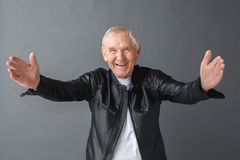 Senior man in leather jacket standing on gray opening hands looking camera friendly close-up royalty free stock photos