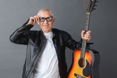 Senior man in leather jacket and sunglasses standing on gray holding guitar touching glasses cool royalty free stock photos