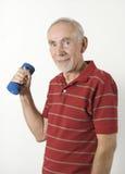Senior man lifting dumbbell. Smiling senior man lifting barbell on white background Royalty Free Stock Photography