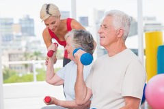Senior man lifting dumbbells while trainer assisting woman at gym. Senior men lifting dumbbells while trainer assisting women in background at gym Royalty Free Stock Images