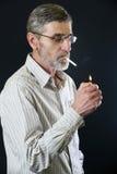 Senior man lighting cigarette Royalty Free Stock Photography