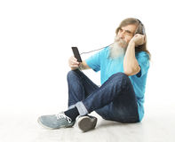 Senior man listening music in phone headphones. Old man beard Royalty Free Stock Photography