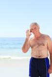 Senior man listening to his shell Royalty Free Stock Image