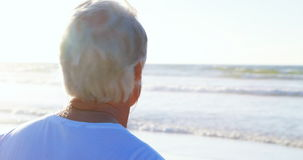 Senior man listening to music on headphones at beach stock footage