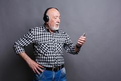 Senior man listening to music with headphones. Senior man listening to music on smartphone with headphones, choosing track on mobile, gray studio background Stock Image