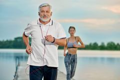 Senior man listening to music, running near lake in the evening. stock image