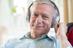 Senior Man Listening To Music On Wireless Headphones Royalty Free Stock Image