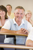 Senior man listening to a university lecture.  Royalty Free Stock Images