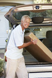 Senior Man Loading Large Package Into Back Of Car Stock Photo