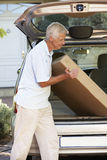 Senior Man Loading Large Package Into Back Of Car Royalty Free Stock Photos