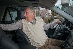 Senior man backing up in car stock images