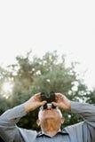 Senior man looking through binoculars Royalty Free Stock Photography