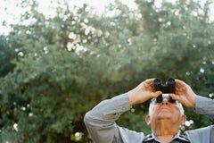 Senior man looking through binoculars Royalty Free Stock Images