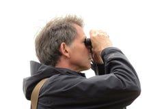 Senior man looking through binoculars Royalty Free Stock Photos