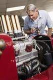 Senior man looking at car engine in automobile repair shop Royalty Free Stock Photos