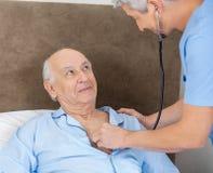 Senior Man Looking At Caretaker Examining Him With. Senior men looking at male caretaker examining him with stethoscope at nursing home stock image