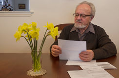 Senior man looking over papers Stock Photography