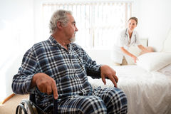 Senior man looking at doctor adjusting bed while sitting on wheelchair Royalty Free Stock Images