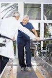 Senior Man Looking At Doctor While Walking In Rehab Center stock image