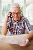 Senior man looking at a document while taking on phone Stock Image