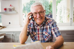 Senior man looking at a document while taking on phone Stock Images