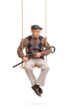 Senior man looking down seated on a swing Stock Photography