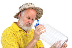 Senior man looking into empty bottle Stock Image