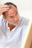 Senior man looking at his hair loss being concerned Stock Images