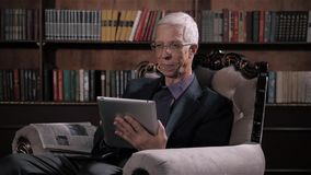 Senior man looking for information on tablet pc in library at home. Happy older man in glasses and modern technology. Senior man looking for information in books stock footage